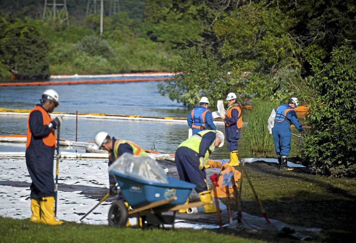 Workers clean oil from the banks of the Kalamazoo River in Marshall, Mich., in July after an Enbridge pipeline ruptured.