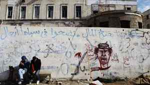 Libyan rebel supporters sit outside rebel headquarters decorated with revolutionary graffiti in the northeastern city of Benghazi, March 23, 2011.