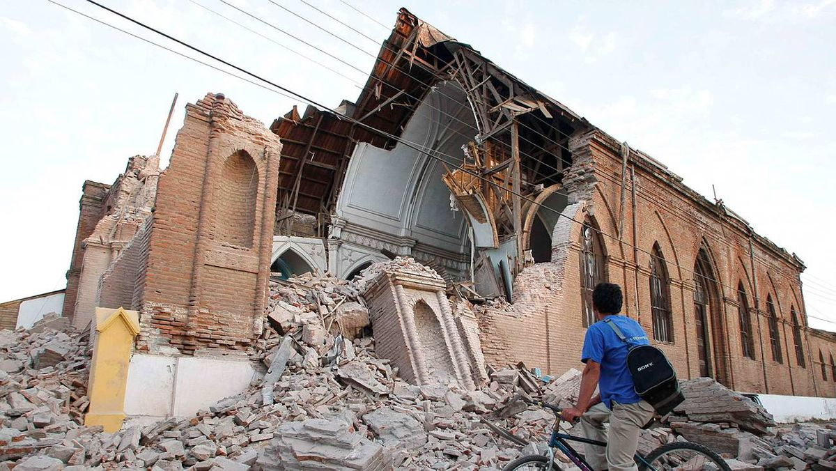 A resident pauses at the San Francisco de Curico church March 1, 2010, after it was damaged in a major earthquake.