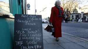 A pedestrian walks past a sign outside a cafe displaying a menu relating to the current economic climate in Dublin on November 23, 2010. The European Union urged Ireland on Tuesday to adopt an austerity budget on time to unlock promised EU/IMF funding, responding to a deepening political crisis that threatens to derail the financial rescue.