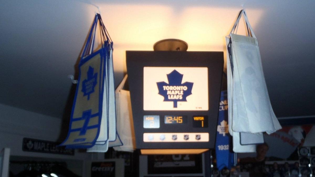The light fixture in Ken LeBlanc's sports memorabilia room is a replica of a Maple Leafs score clock