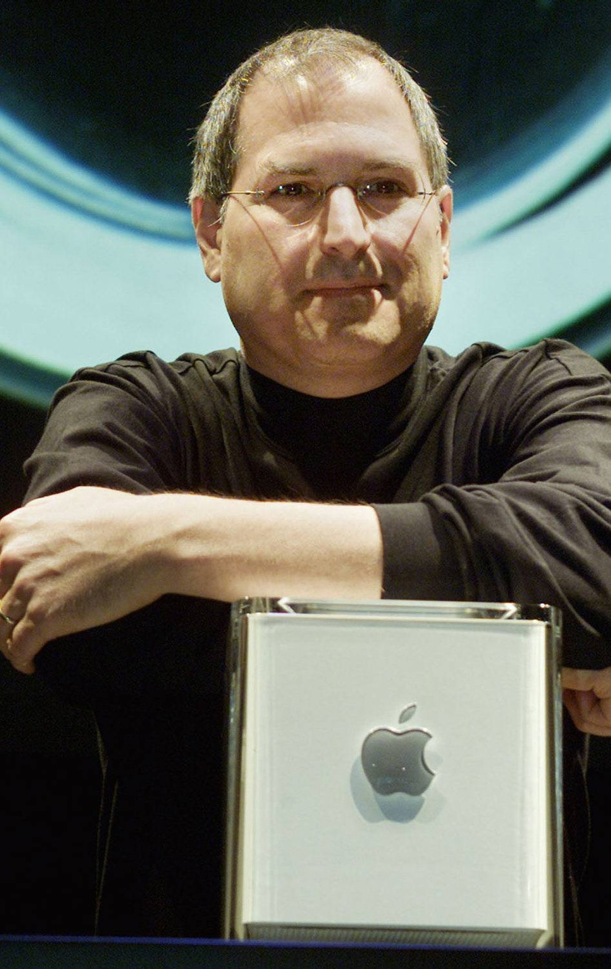 Apple Computer Inc. founder Steve Jobs poses with the company's new Power Mac G4 Cube, after his keynote adddress at the Macworld Conference and Exposition in New York on July 19. The G4 Cube, which Jobs said combines the power of the Power Mac G4 with the style and miniaturization of an iMac, comes in an 8-inch cube suspended in a clear enclosure.