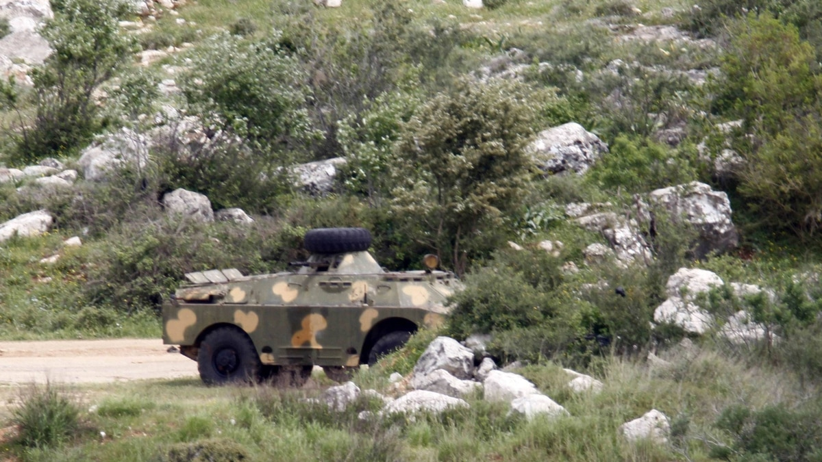 Syrian armoured personnel carriers are seen at the Wadi Khalid area near the Syrian border in northern Lebanon April 12, 2012.