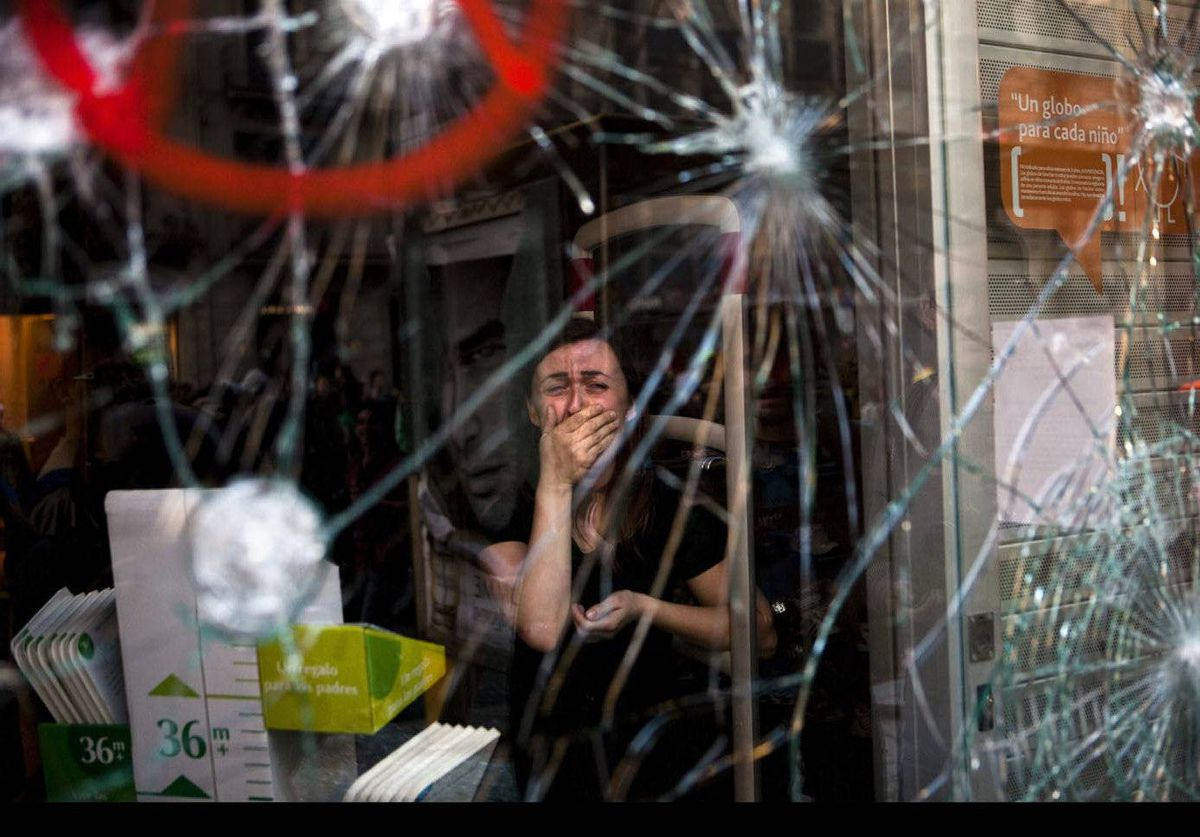 Mirian Burrueco, 30, reacts behind the broken glass of her shop which was attacked by demonstrators during clashes with police during a general strike in Barcelona, Spain.