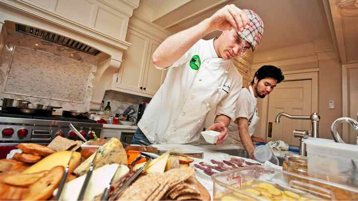 Chef Chris Brown, left, runs The Stop Community Food Centre's catering service. He and Miguel Iraheta, right, prepare dinner for 15 at a private birthday party in a Toronto home on Nov. 12, 2011.