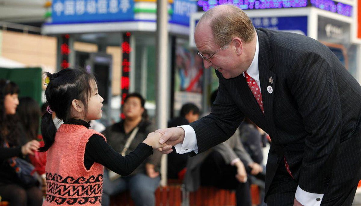 Manulife CEO Don Guloien, shakes hand with He Xing Chen, 5, at the Shanghai Expo