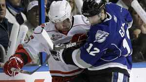 Tampa Bay Lightning left wing Simon Gagne (12) and Carolina Hurricanes right wing Erik Cole (26) battle for a loose puck along the boards during the first period of an NHL hockey game, Saturday, Feb. 12, 2011, in Tampa, Fla. The Lightning won 4-3 in overtime. (AP Photo/Chris O'Meara)