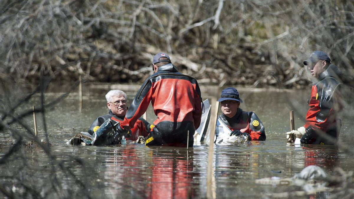 Members of an RCMP underwater recovery team search Sunday May 12, 2012, at the site where one of two planes crashed Saturday near St. Brieux, Sask.