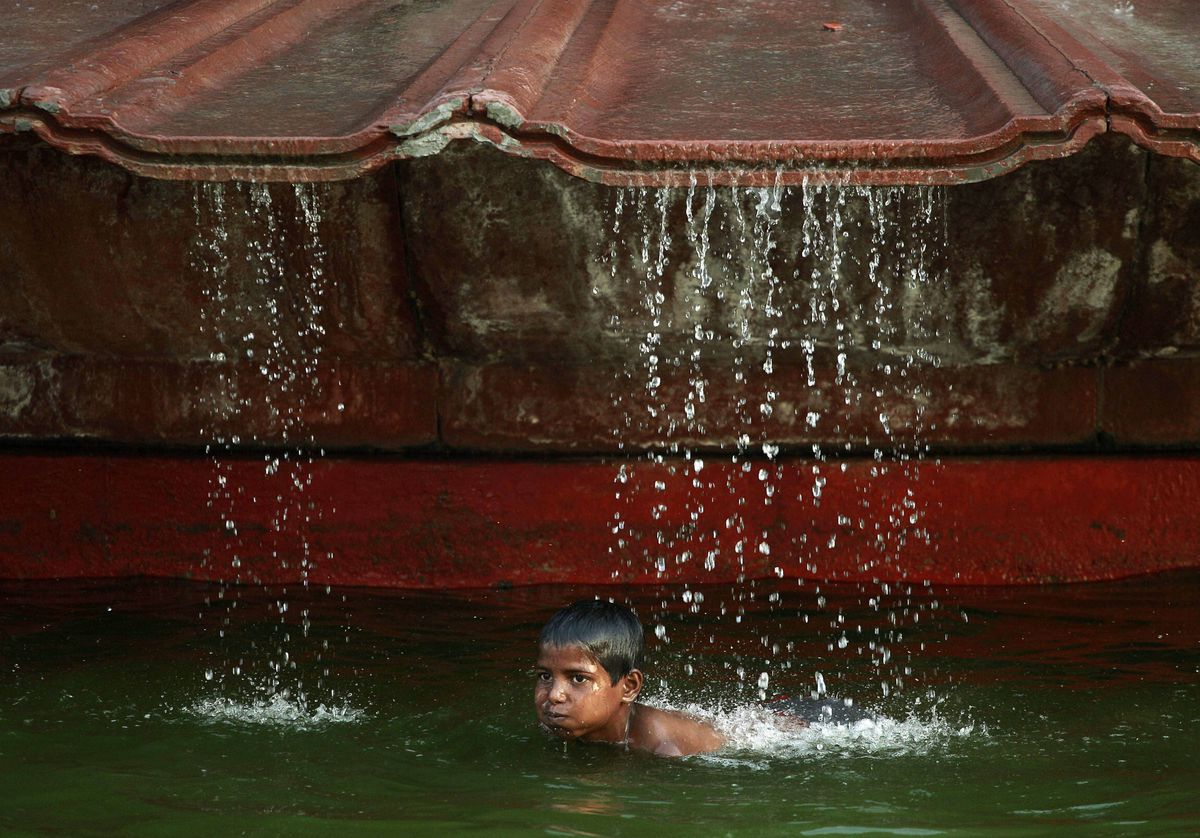 An Indian boy cools off in a fountain at the India Gate Monument on a warm day in New Delhi, India. Temperatures in India's capital soared to 43 degree Celsius Wednesday after unseasonably cool temperatures over the last month.