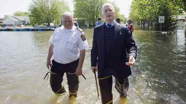 NDP leader Jack Layton, right, takes a walk along a street immersed in flood waters alongside St-Paul fire chief Gilles Bastien in the town of St-Paul-de-I'lle-aux-Noix, Que., Monday, May 30, 2011.