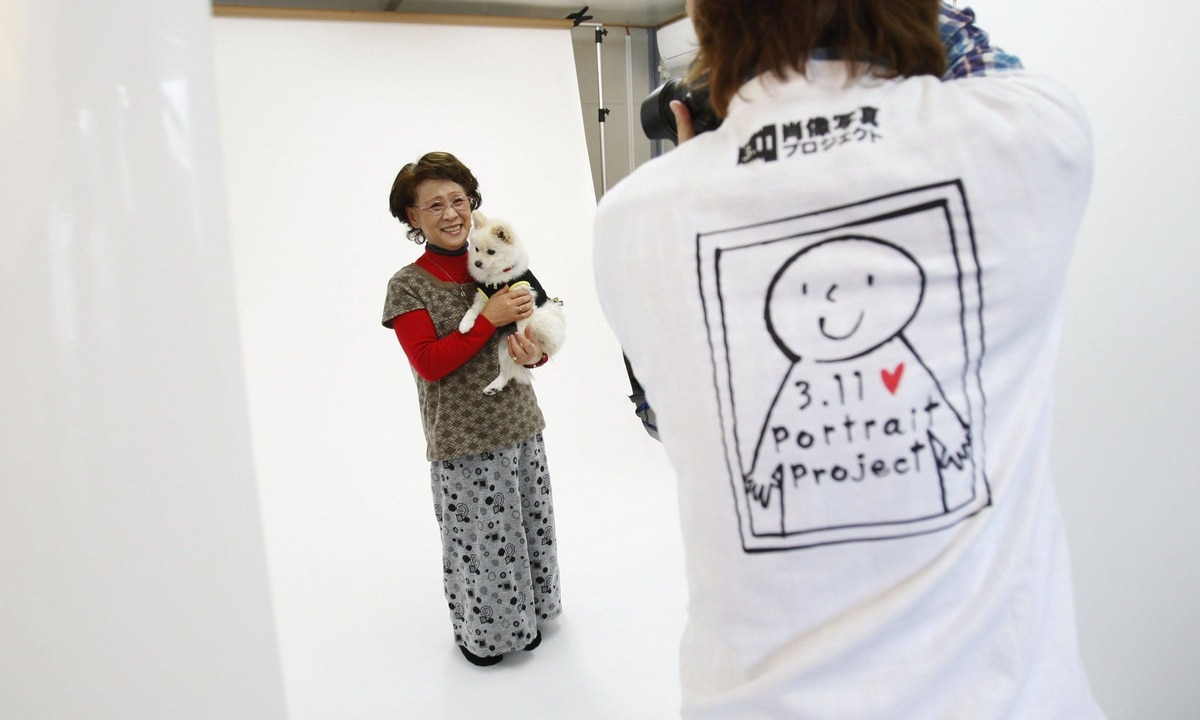 Photographer Kenichi Funada takes a portrait of Katsuko Abe with her pet dog Kaede as part of the 3.11 Portrait Project. The project was conceived by photographer Nobuyuki Kobayashi who takes portraits of Japan's earthquake survivors. The portraits are then sent to schoolchildren from non-disaster areas, who frame the portraits and send them back to the survivors along with personal messages of support.