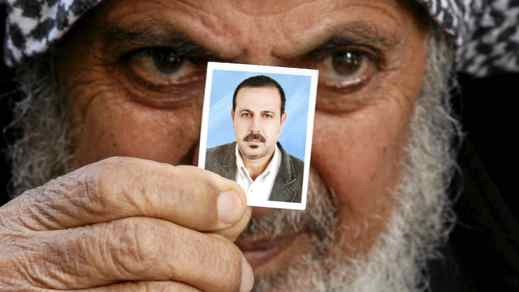 The father of Palestinian militant Mahmoud al-Mabhouh, who was killed in January, holds a photo of his son at the Jebaliya refugee camp in the Gaza Strip.