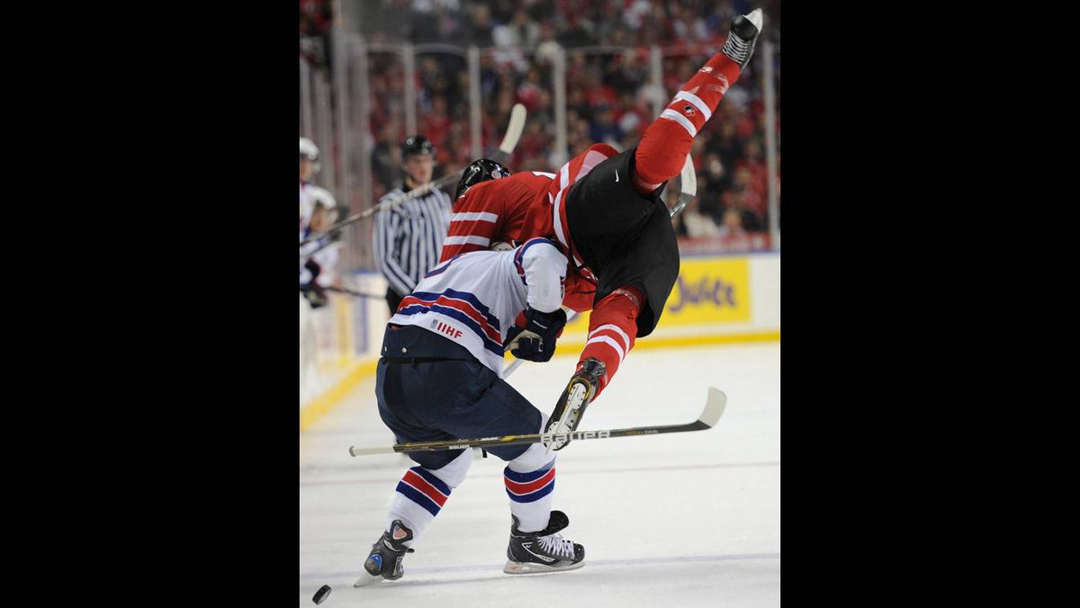 Team Canada's Quinton Howden, right, crashes into Team United States John Ramage during first period semi-final action.