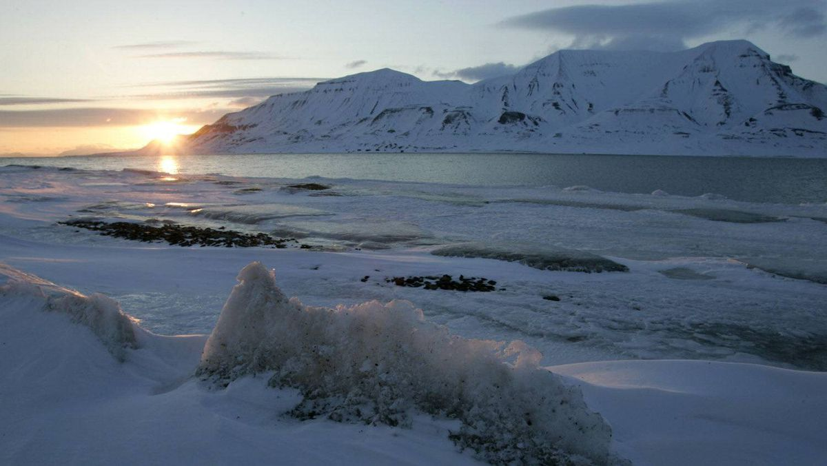The sun shines low in the sky just after midnight over a frozen coastline near the Norwegian Arctic town of Longyearbyen in this April 26, 2007 file photo.