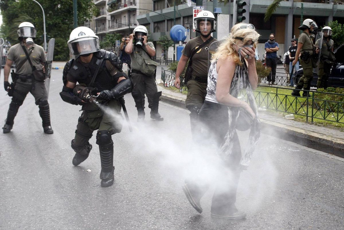 A policeman sprays tear gas as a protester walks away during an anti-austerity rally in Athens June 29, 2011. Anti-austerity protesters attempted to block streets leading to the parliament where later today, Greece's parliament holds a crucial vote on whether to submit the country to a fresh wave of unpopular austerity measures as it attempts to avoid a debt default. REUTERS/Panagiotis Tzamaros (GREECE - Tags: POLITICS BUSINESS CIVIL UNREST CRIME LAW)