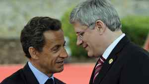 French President Nicolas Sarkozy speaks to Prime Minister Stephen Harper upon arrival at the G8 summit in Deauville, France, on May 26, 2011.