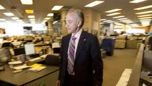 File photo of Postmedia Network Inc. CEO Paul Godfrey walking through the National Post newsroom in Toronto.