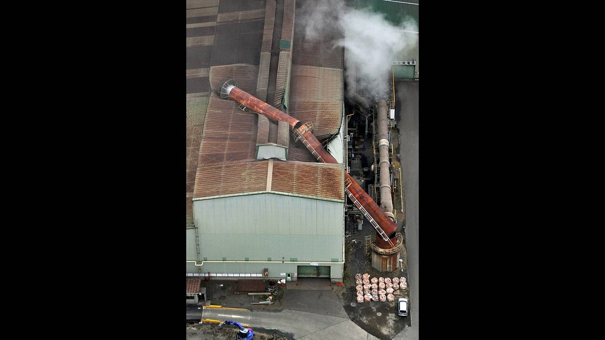 A chimney falls onto its factory in Sendai, Miyagi prefecture, Japan, after one of the largest earthquakes on record slammed Japan's eastern coasts Friday, March 11, 2011.