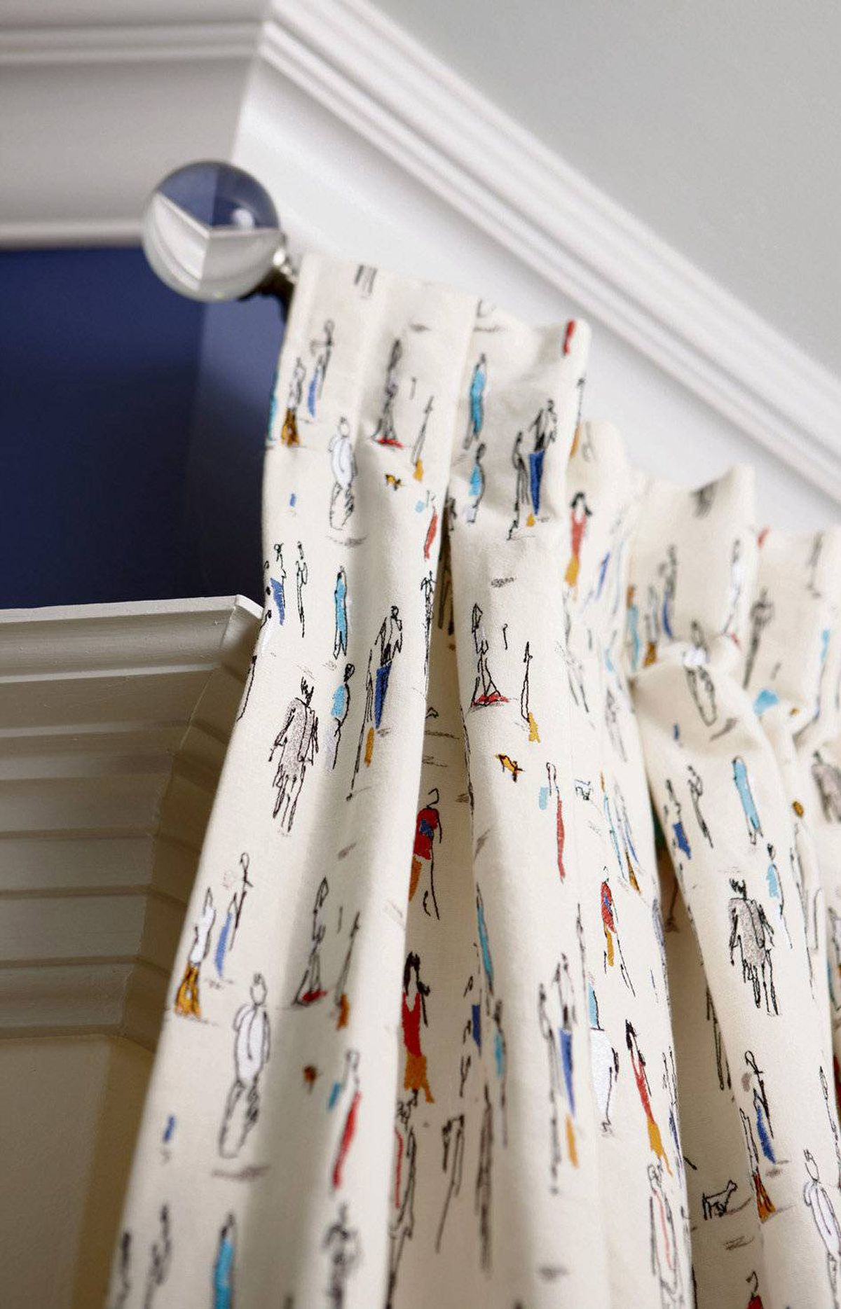 INJECT SOME SPIRIT Instead of playing it safe and serious, go for energetic, lighthearted drapery fabric. Here, embroidered street scenes of line-drawn people have an urban graffiti-style edge that appeals to the younger set and is well suited to a room that's supposed to encourage frivolity.