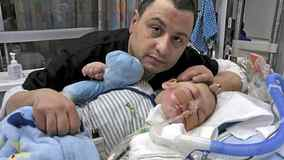 Moe Maraachli, sits by his terminally ill baby, Joseph. The baby is being kept alive in by a breathing tube in a London hospital.