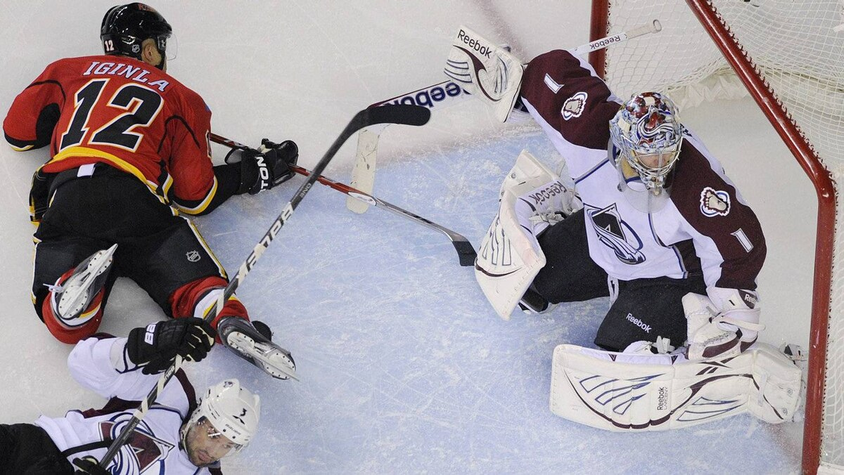 Calgary Flames' Jarome Iginla (12) is knocked down in front of Colorado Avalanche's goalie Semyon Varlamov (R) by Ryan O'Byrne during the third period of their NHL hockey game in Calgary, Alberta March 30, 2012. REUTERS/Todd Korol