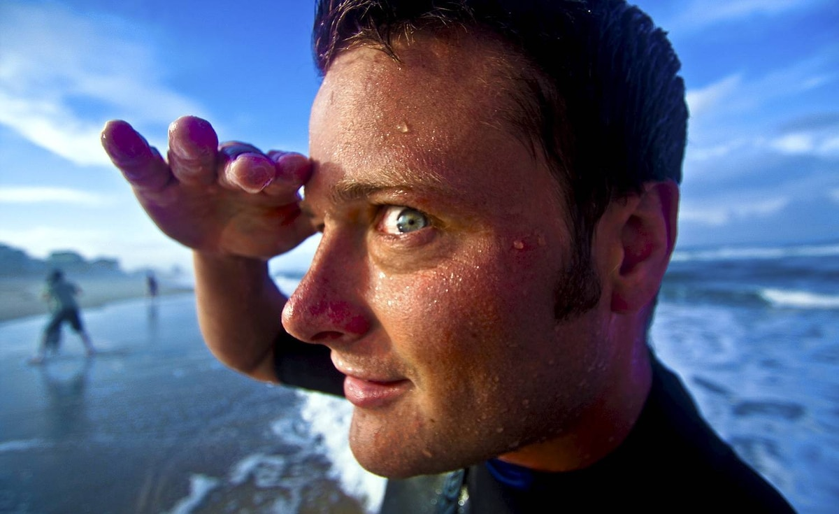 "Rohit Saxena of Ottawa (The.Rohit on Flickr) uploaded this image to our pool: ""Caught my friend Matt McKee mugging for the camera as we surfed the beaches of the Outer Banks in North Carolina. The colours and the exaggerated perspective on his arm and eye really catch my attention, hopefully you guys like it too."""
