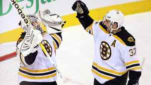 Boston Bruins goalie Tim Thomas (30) celebrates with teammate Patrice Bergeron after defeating the Montreal Canadiens 1-0 in National Hockey League action Monday, November 21, 2011 in Montreal.