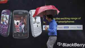A man tries to hold on to his umbrella as he walks past a Blackberry advertisement billboard in Mumbai.