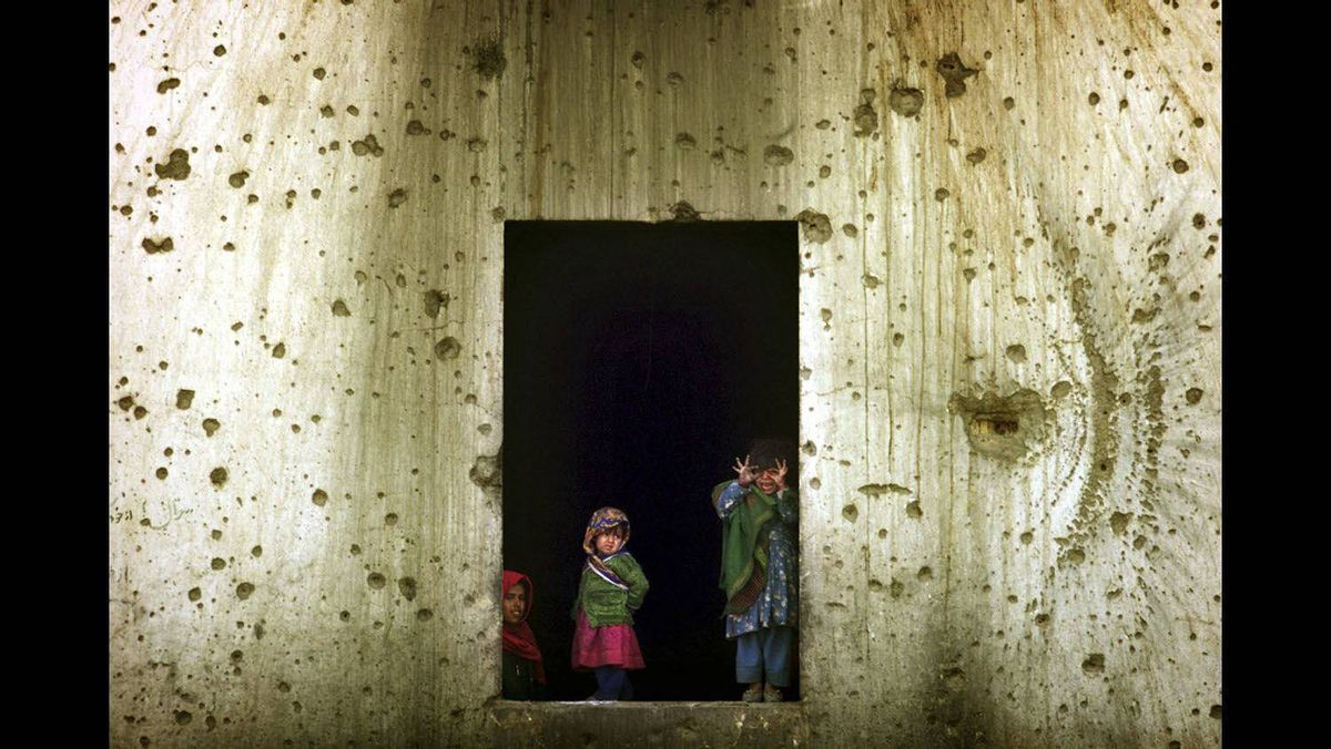 Afghan refugee children look from the window of their shelter in the former Soviet embassy, a huge compound amid the destruction of west Kabul, November 27, 2001.