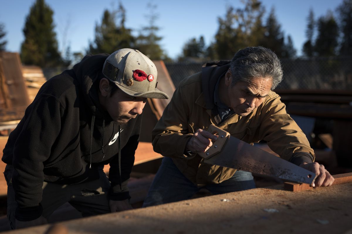 Carver Joe Martin shows David Curley some of the final steps for shaping a canoe hull.