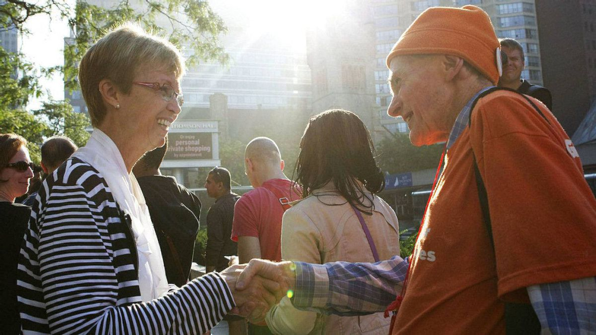 NDP interim leader Nycole Turmel (left) greets people who have queued for a public ticket to attend the funeral of late NDP leader Jack Layton's at Roy Thompson Hall.