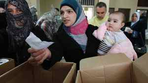 Syrian refugees receive humanitarian aid from an Islamic organization in Tripoli, northern Lebanon, March 6, 2012.