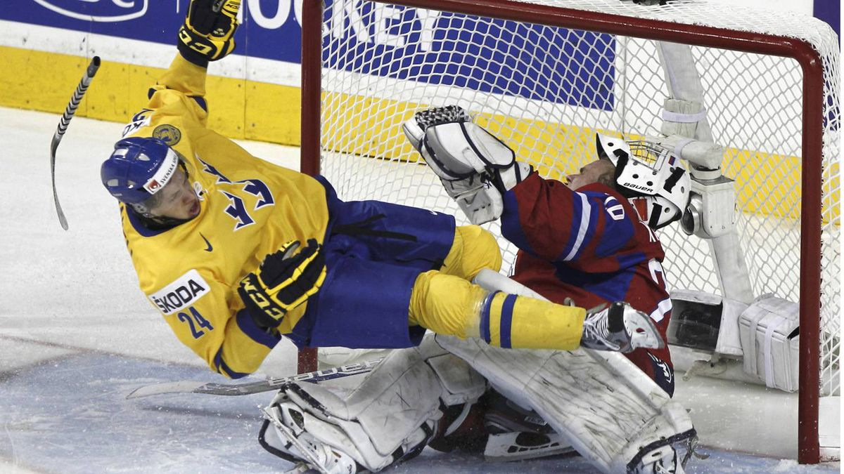 Sweden's Rickard Rakell crashes into Russia's goalie Andrei Makarov in the third period.