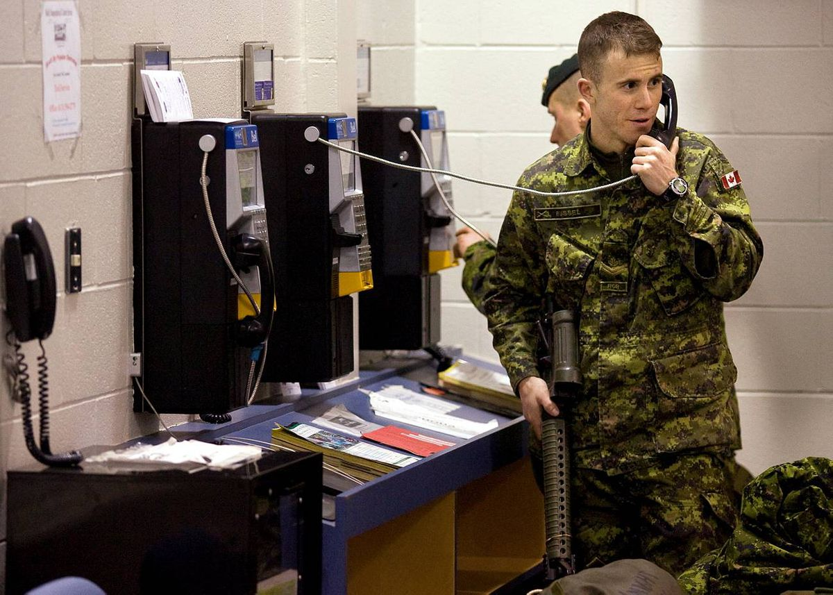 Master Corporal Dan Russel speaks to his wife on the phone at CFB Trenton before leaving on a Disaster Assistance Response Team ( DART) humanitarian mission to earthquake ravaged Haiti on Wednesday. THE CANADIAN PRESS/Darren Calabrese