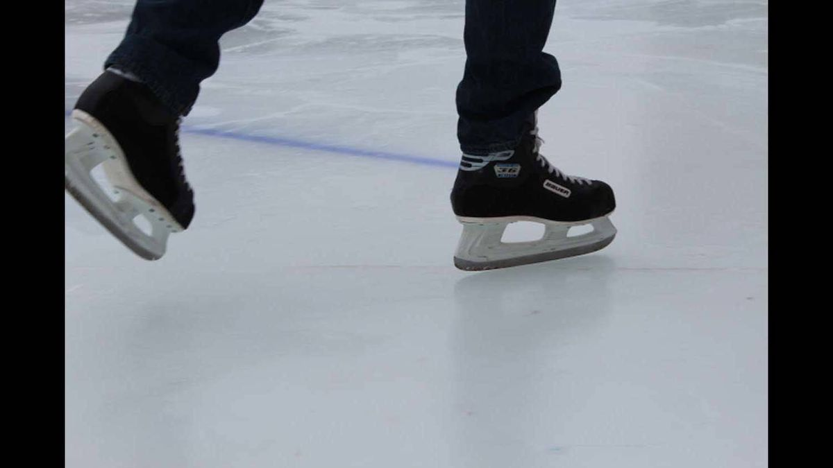 Close up of the skates, as they are moving across the ice