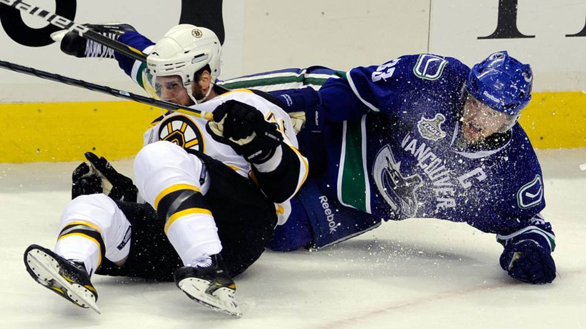 Henrik Sedin of the Vancouver Canucks collides with David Krejci of the Boston Bruins during Game 5.