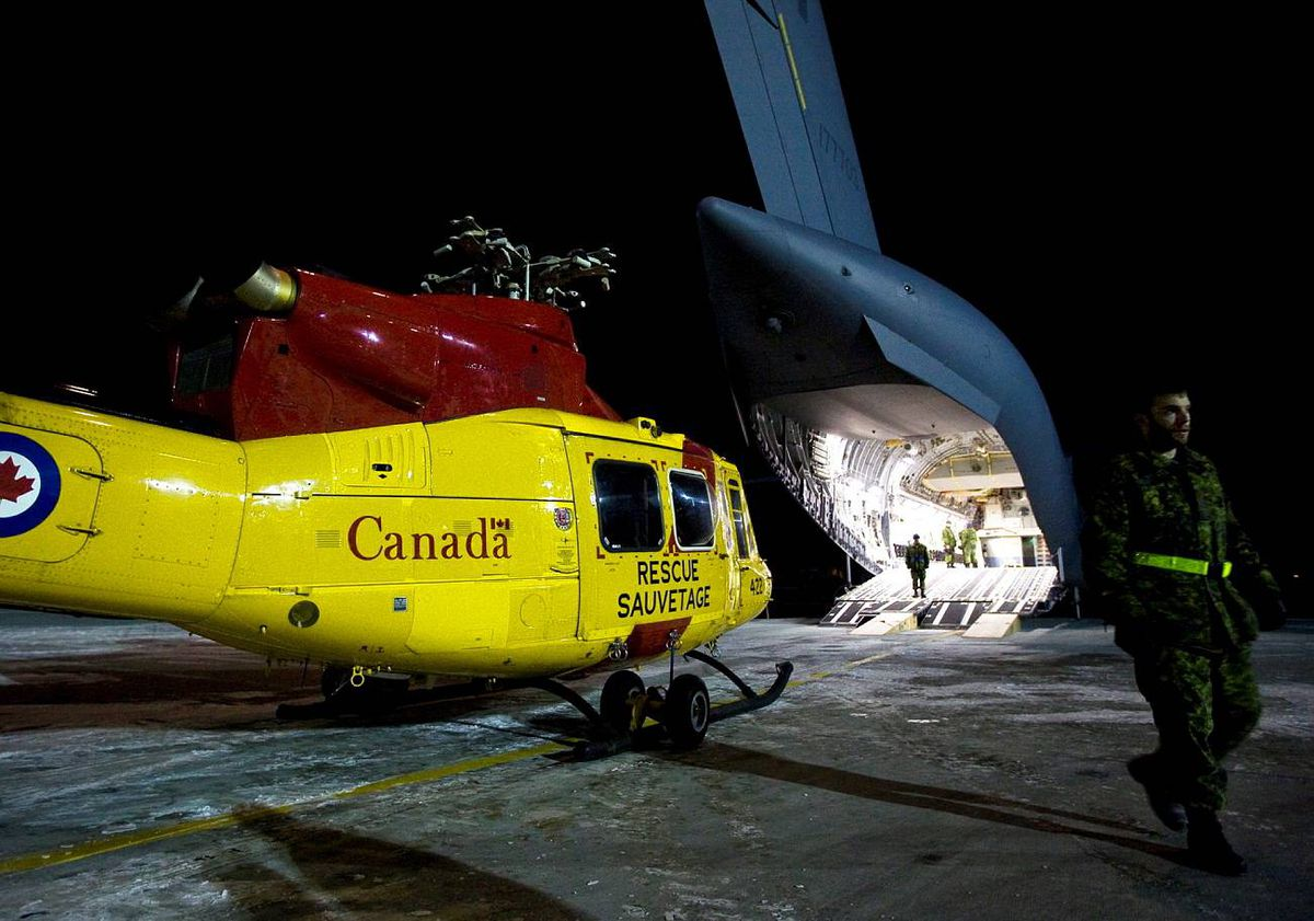 Military personnel prepare to load a Griffin helicopter on a CC-177 Globemaster on the tarmac at CFB Trenton for a Disaster Assistance Response Team ( DART) humanitarian mission to earthquake ravaged Haiti on Wednesday, January 13, 2010. THE CANADIAN PRESS/Darren Calabrese