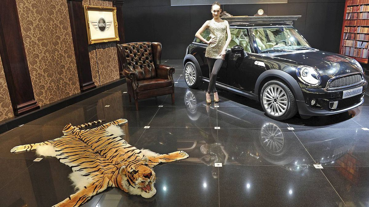 A Chinese model poses by a Mini at the Shanghai Auto Show in Shanghai on April 19, 2011. About 2,000 car and parts makers from 20 countries are participating in the Shanghai auto show, showcasing 75 new car models, 19 of them making their world premieres. AFP PHOTO/Philippe Lopez (Photo credit should read PHILIPPE LOPEZ/AFP/Getty Images)