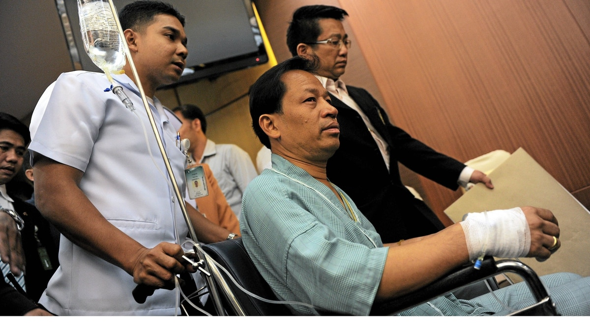 Thai opposition politician Pracha Prasopdee, centre, leaves in a wheelchair after addressing a press conference at a hospital in Bangkok on May 12, 2011, two days after he was shot in the back in the outskirts of the Thai capital.