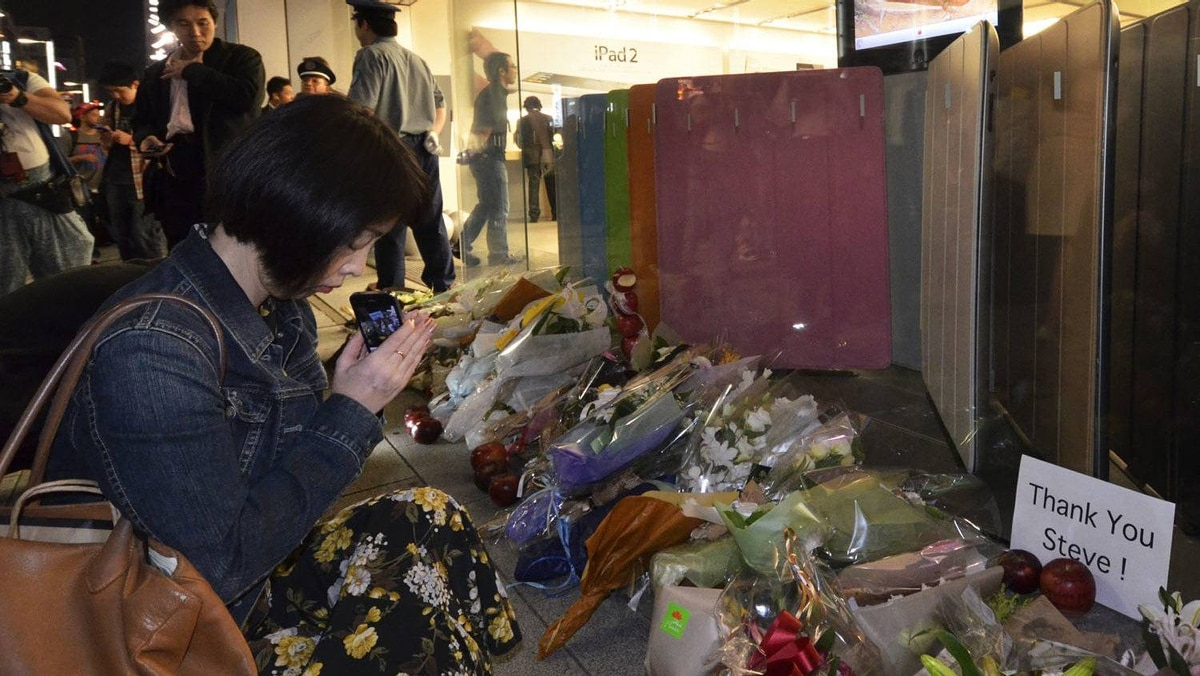 A woman prays near flower bouquets paying tribute to Apple co-founder Steve Jobs outside an Apple store in Tokyo on October 6, 2011.