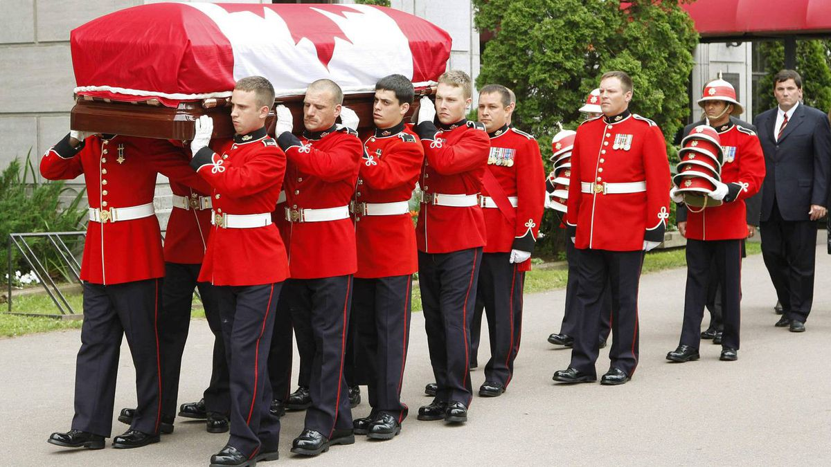 Members of the Royal Canadian Regiment carry the casket containing the remains of Romeo LeBlanc, former governor-general of Canada, out of the Memramcook Institute toward a hearse for transport to a state funeral service at Saint Thomas church in Memramcook, NB.