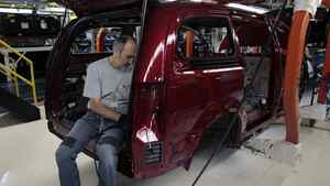 A Chrysler auto assembly worker assembles the new 2011 Dodge Grand Caravan's and Chrysler Town & Country minivans at the Windsor Assembly Plant in Windsor, Ontario January 18, 2011.