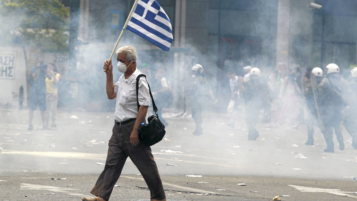 A protester holds a Greek as he walks in tear gas outside of the Greek Parliament in central Athens, during a rally against plans for new austerity measures, June 15, 2011.