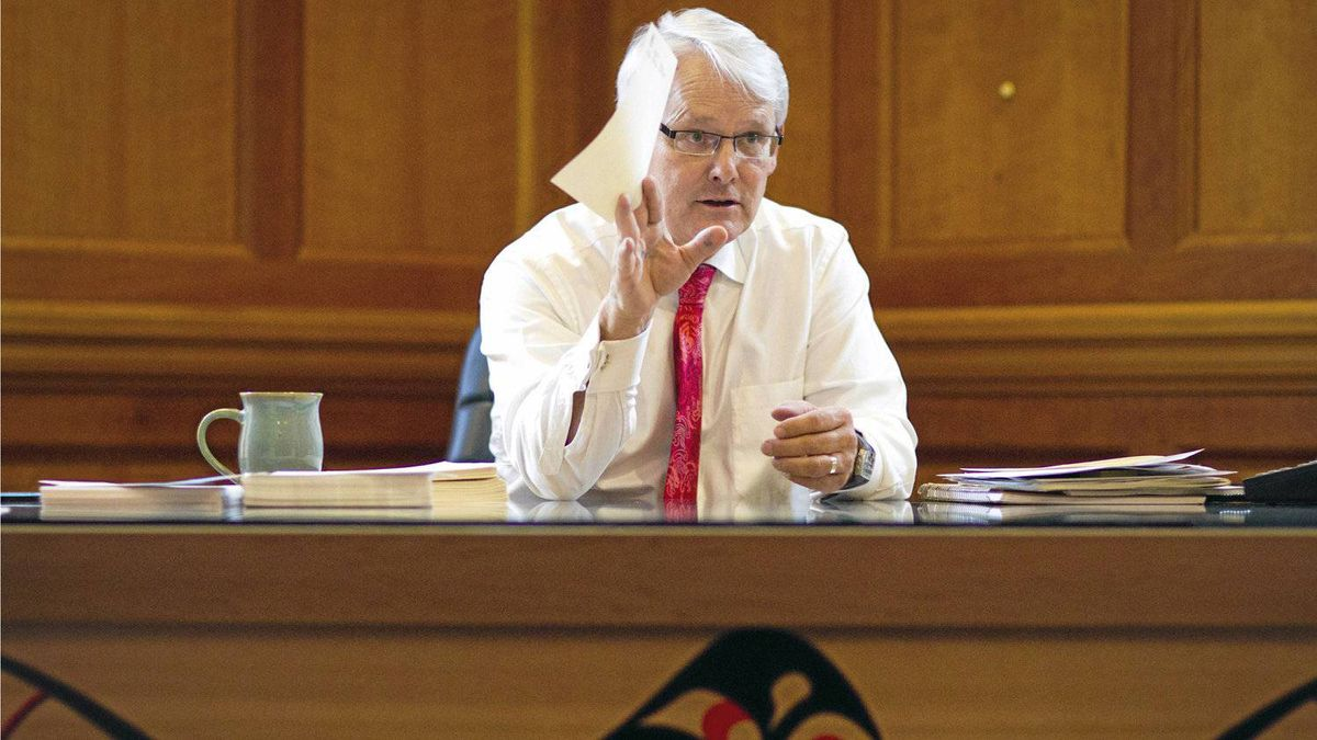 """Outgoing B.C. Premier Gordon Campbell sits behind the """"Leadership Desk"""" at his office in Victoria. The hand-crafted red cedar desk, created in the form of a bentwood box and adorned with First Nation's iconography, was designed by internationally-known B.C. artist Arthur Vickers."""