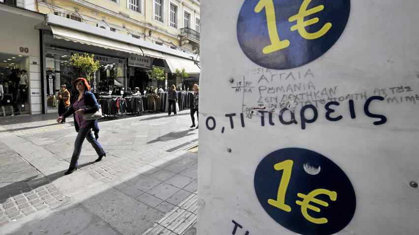 A woman walks past a '1 Euro' shop in Athens in November, 2011. Pro-austerity parties in Greece failed to win enough support from voters to form a government this month, and neither did their anti-austerity opponents.