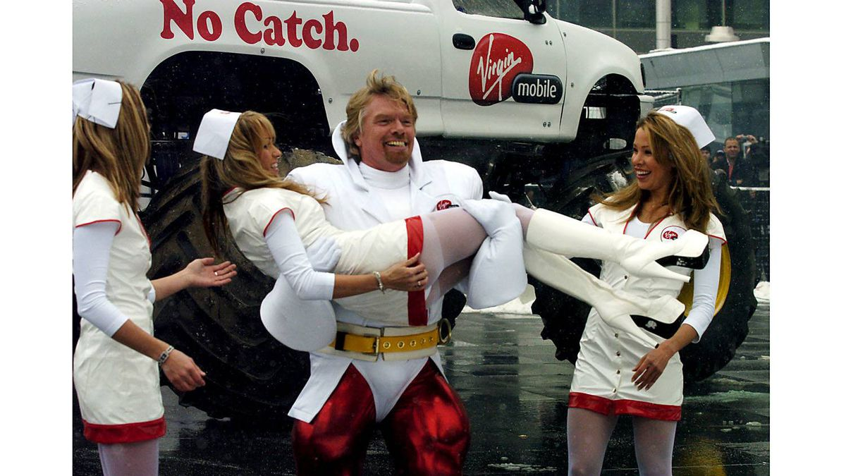 The monster truck is a natural Woman-Repeller. Bear in mind that the man in this picture is billionaire Richard Branson, and that these women are with him because: (A) he's Richard Branson, owner of a private island, a worldwide empire, and a fleet of cars that women actually like, and (B) because they're professional models who will appear with a monster truck if the money is right. (Actually riding in it would cost more.)